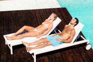 Peaceful couple sunbathing on deck chairs