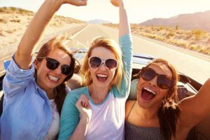 Three Female Friends On Road Trip In Back Of Convertible Car